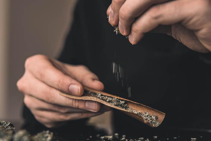 Personne roulant un joint de cannabis- Arrêter le cannabis avec le cbd